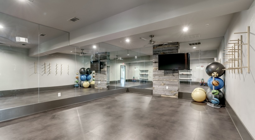 Our yoga studio with HDTV, wall mirrors, and light exercise equipment at our luxury apartments near Legacy West