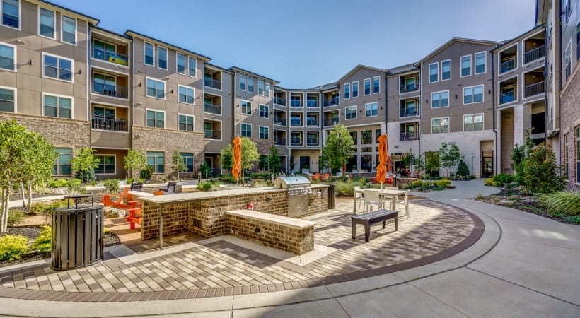 Courtyard with string lights, chairs, and paver walkway at Circa apartments near Legacy West