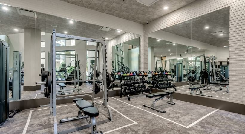 Wide range of weights and wall mirrors at our 24/7 fitness center at our luxury apartments in West Plano, TX