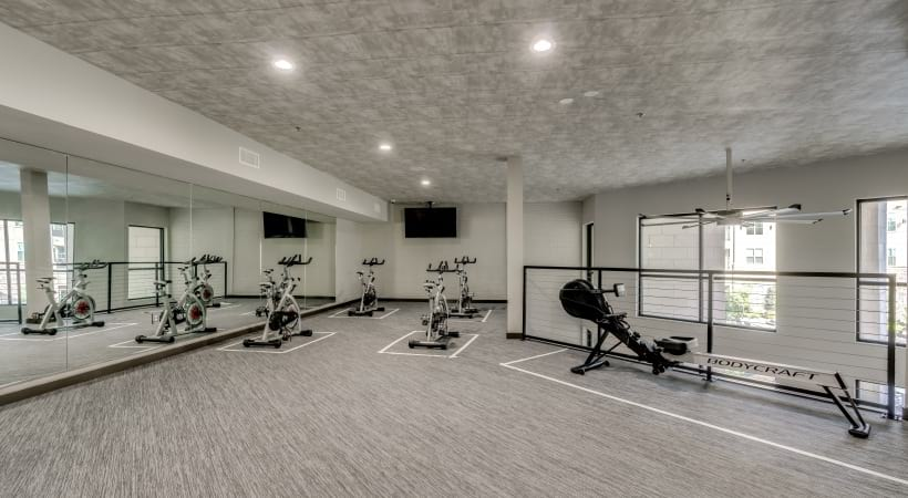 Second floor of our spacious fitness center with treadmills, a rowing machine, and an HDTV at Circa Apartments in Frisco, TX
