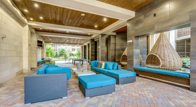 Sundeck with comfortable patio sets and hanging rattan chairs at our Verus Frisco luxury apartments near Shops at Legacy