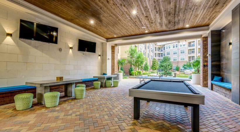 Outdoor lounge with games like jenga and billiards at Cortland Verus Frisco apartments near Legacy West