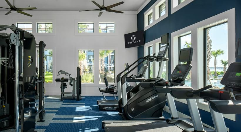 Our Clearwater apartment gym with ceiling fans and large windows