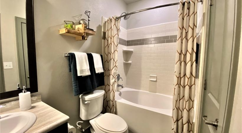 Spacious apartment bathroom with deep soaking bathtub
