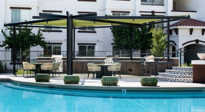 Resort style pool with sun deck at apartments in East Mesa