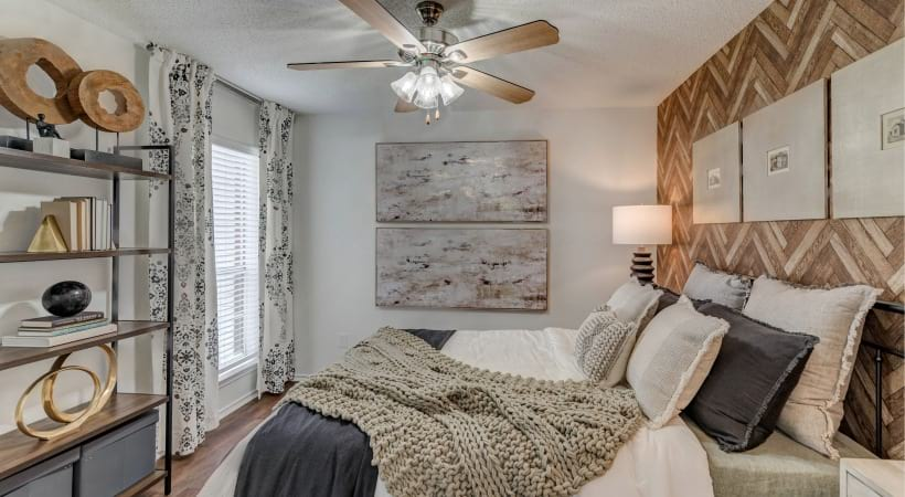 Bedroom with ceiling fan and cozy decor at our apartments in Irving, TX