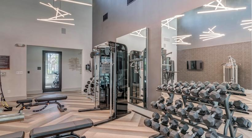 Gym with free weights at our Cortland La Villita apartments in Irving, TX