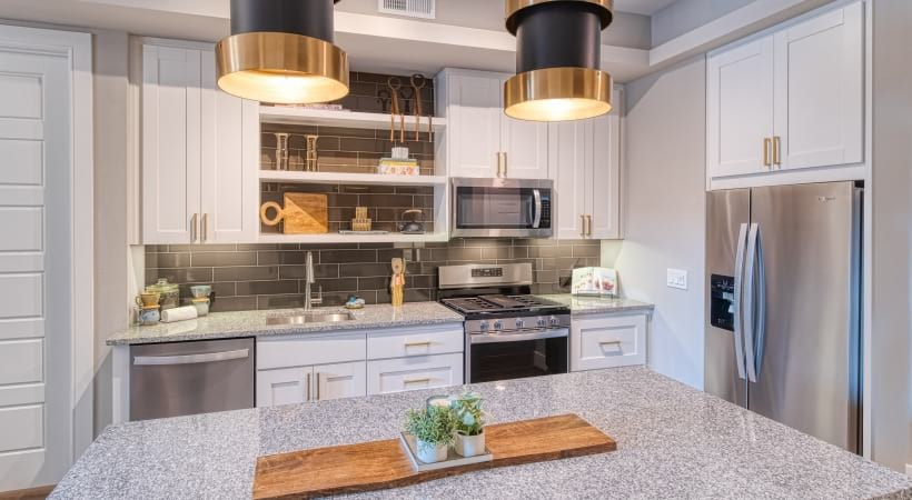 White Cabinetry with Gold Hardware and Designer Tile Backsplashes at Cortland Biltmore Apartments