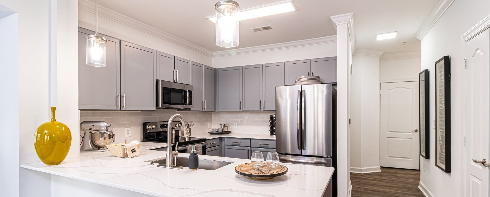 Upscale Kitchen With Quartz Breakfast Bar And Modern Lighting At Our North Druid Hills Apartments