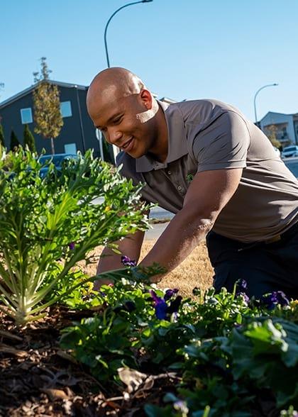 Service Tech Planting Flowers