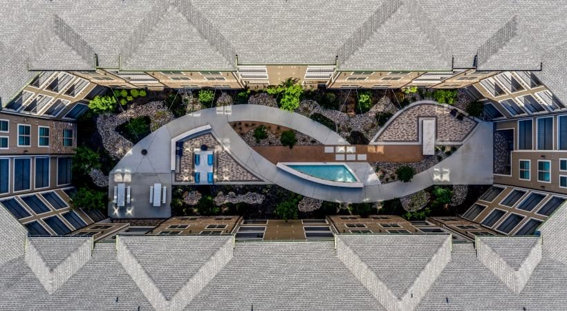 Aerial view of our courtyard with paver walkway and seatings at our Frisco apartments near Stonebriar Mall