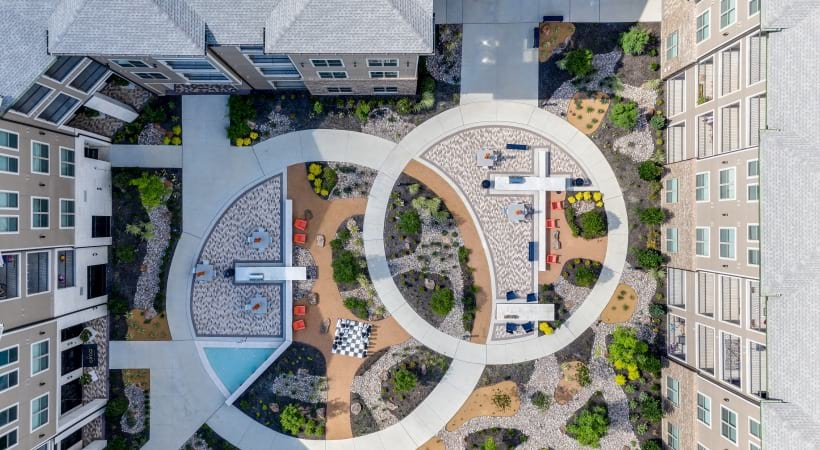 Aerial view of our courtyard with outdoor kitchen, beautiful landscape, and dining areas at our modern apartments in West Plano, TX