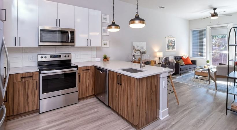 Modern Kitchen With Two-Toned Cabinets And Stainless Steel Appliances At Our Apartments Near Briarcliff Road