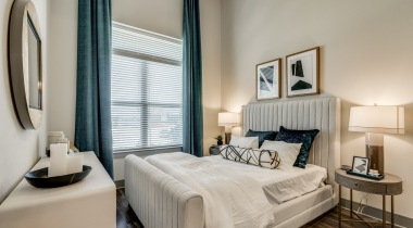 Modern bedroom with wide windows and cozy home decor at our luxury apartments in West Plano, TX