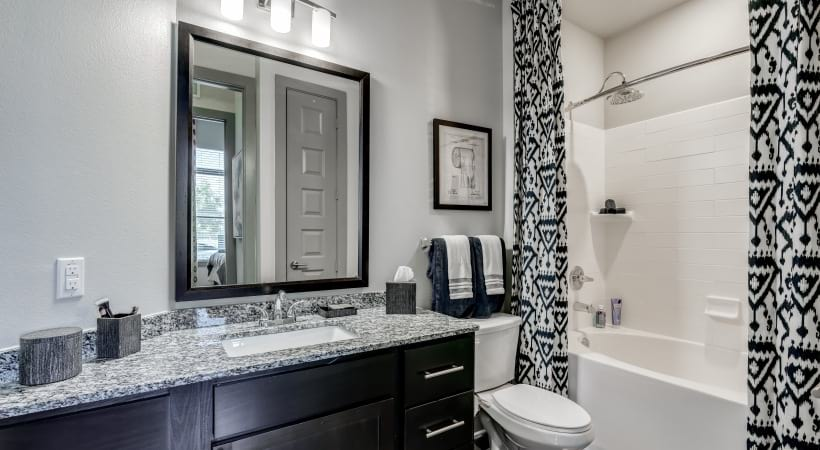 Bathroom with granite countertops and deep-soaking bathtubs at our luxury apartments in West Plano, TX