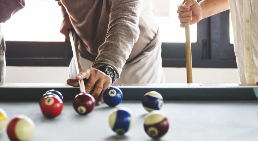 Attiva Central Park apartment residents playing pool at the clubhouse of our active adult community in Grand Prairie, TX