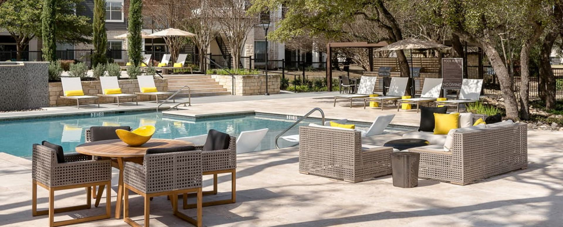 Poolside lounge chairs and umbrellas at our upscale apartments in Round Rock, TX