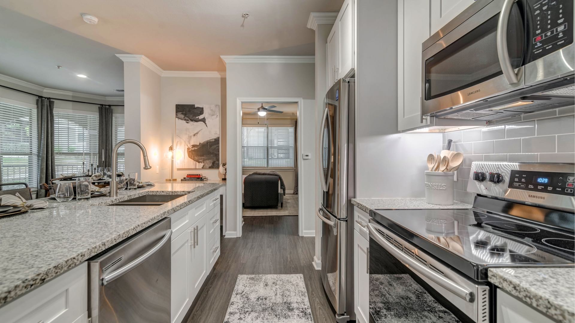 Luxury kitchen with white cabinets, granite countertops, and stainless steel appliances at our apartments for rent in Euless, TX