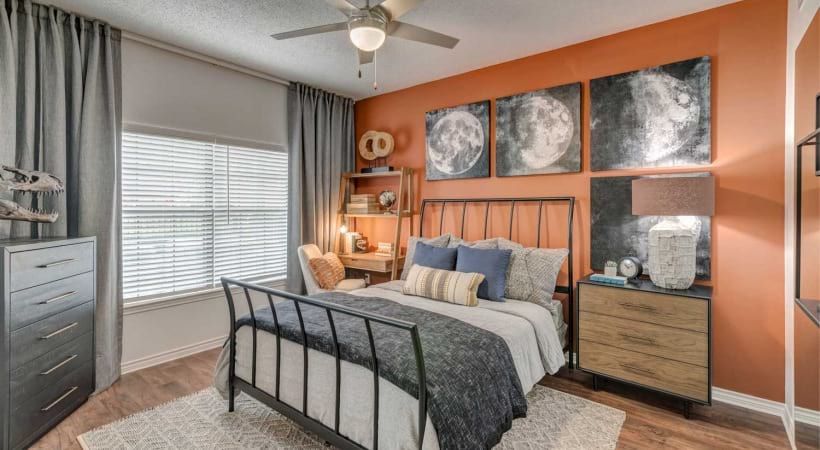 Modern bedroom with wide windows and wood-style flooring at our luxury apartments in Irving