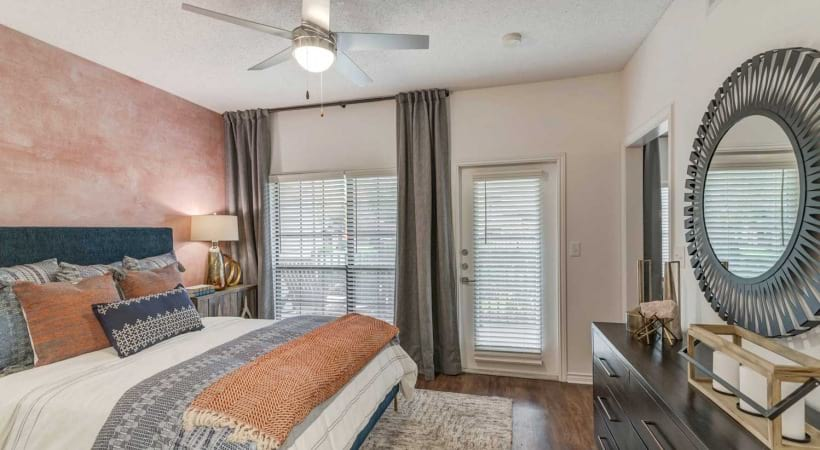 Upscale apartment bedroom with door that leads to personal patio at our apartments in Valley Ranch - Irving