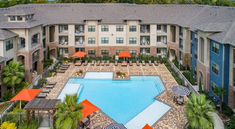 Resort style pool with sun deck at apartments in Katy, TX