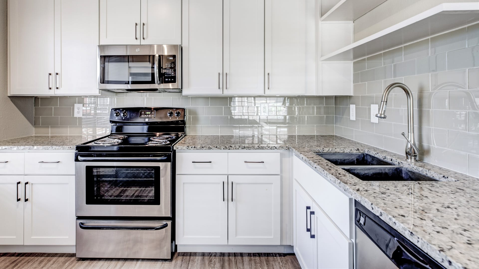 Kitchen with white cabinets at our modern apartments in Cherry Creek, CO