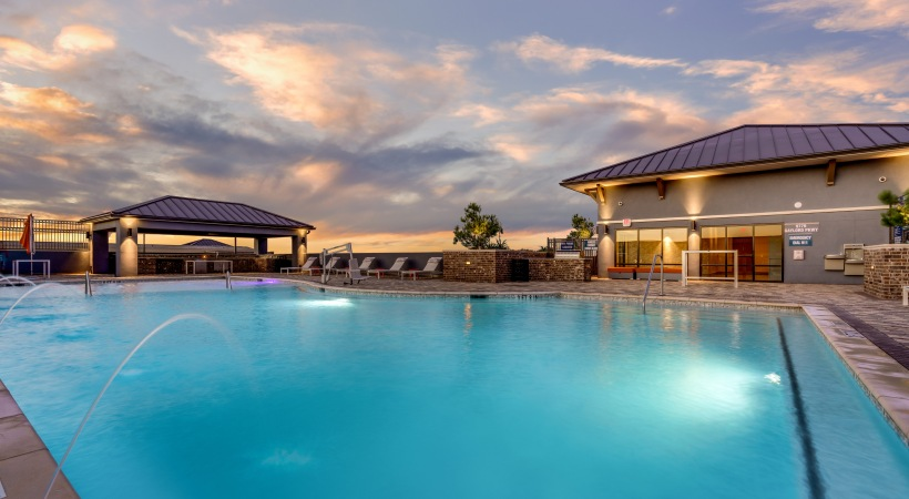 Saltwater, resort-style pool with night lighting at our modern apartments in Frisco, TX
