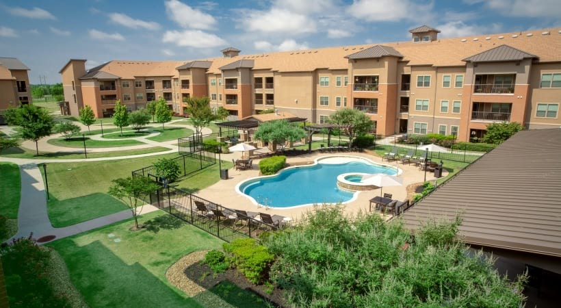 Aerial view of the apartment pool at our 55 and older apartments for rent in Grand Prairie, TX